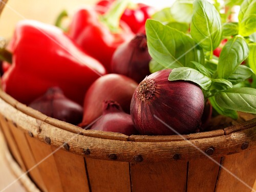 Red onions, peppers and basil in a wooden basket