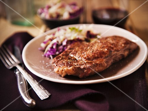 Grass Fed Rib-Eye Steak Served with Cabbage Salad and Red Wine