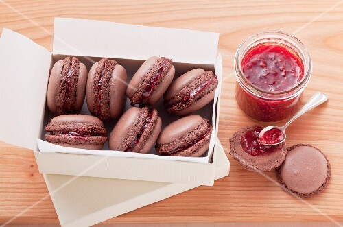 Chocolate macaroons filled with raspberry jam, in a white cardboard box