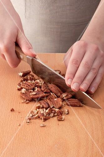 Hände hacken Pekannüsse mit einem großen Messer