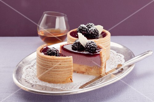Two Baumkuchen (German layer cakes) filled with blackberry cream, and a glass of whisky
