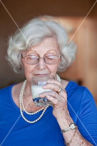 An older woman drinking a glass of milk