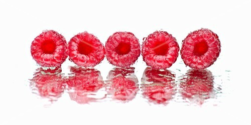 A row of raspberries on a wet mirror