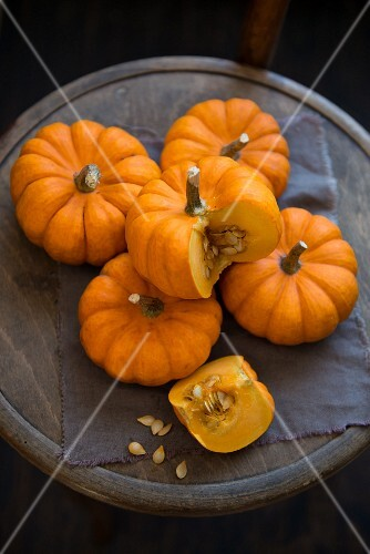 Five pumpkins on a round wooden chair, one sliced