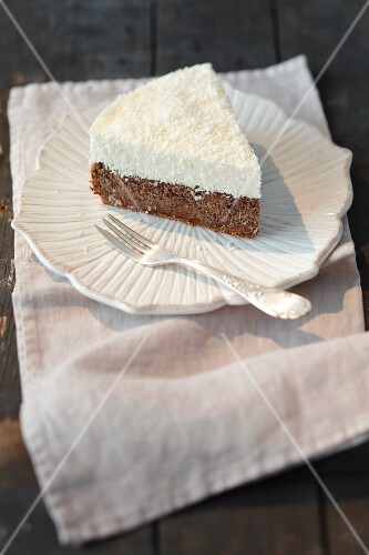 A piece of poppy seed cake topped with coconut mousse
