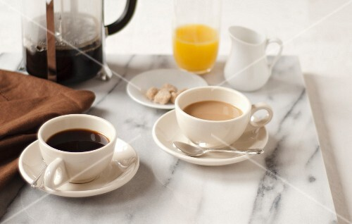 Two Cups of Coffee with a French Press and Orange Juice