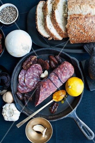 An arrangement of bread, salami, dates, vegetables and spices