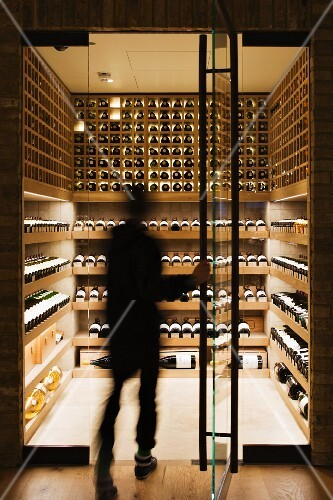 Person entering a modern wine cellar