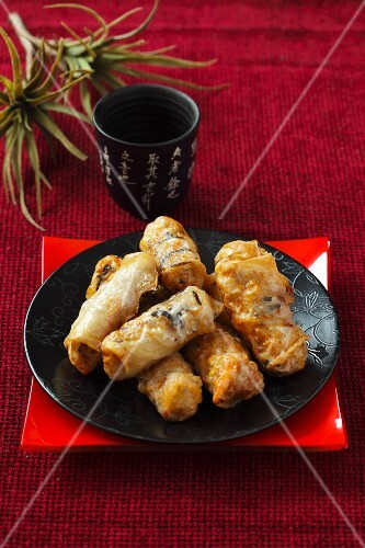 Fried spring rolls on a black plate on a red surface