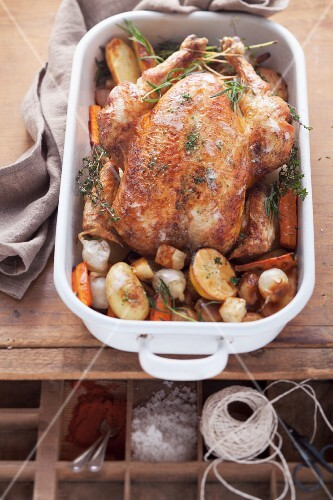 Roast chicken with root vegetables in a roasting dish, seen from above