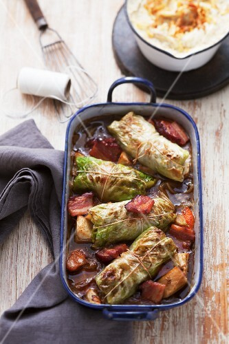 Cabbage roulade in a roasting dish with vegetables, seen from above