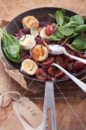 Pflaumenkompott mit gebratenem Ziegenkäse und frischen Spinatblättern in einer Pfanne