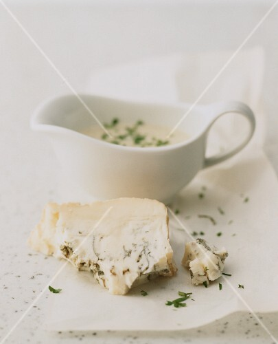 A slice of blue cheese and cheese sauce in a gravy boat