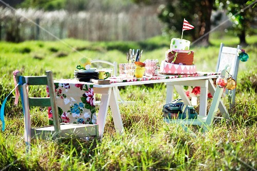 Tiered cake with flag and crockery for child's birthday party on simple wooden table in meadow