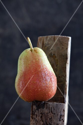 A wet pear on a wooden surface