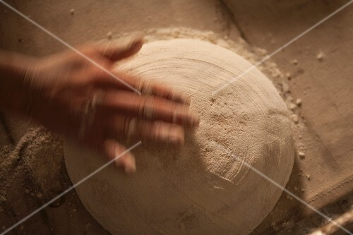 A hand sprinkling an unbaked loaf with flour