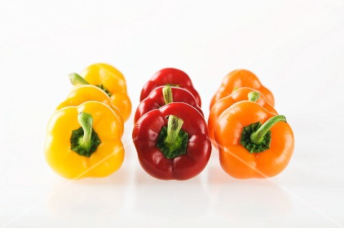 Rows of red, yellow and orange peppers arrange by colour