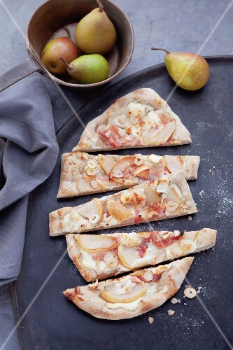 Tarte flambée topped with pears, sliced