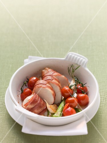 Chicken breast wrapped in ham with cherry tomatoes and spring onions