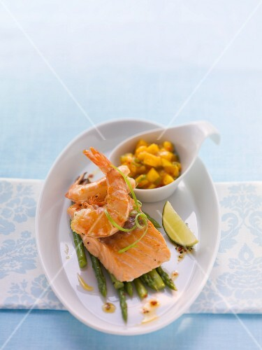 Fried salmon with prawns on a bed of asparagus with mango salsa