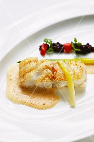 Fried cod with lentils, tomato broth and leek