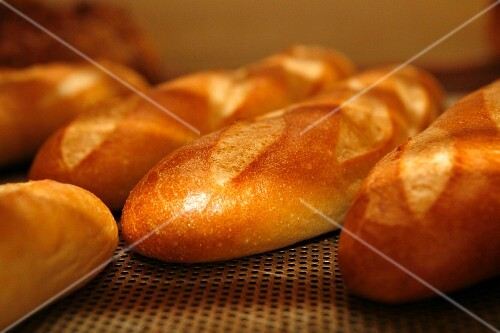 Baguettes cooling on a wire rack in a bakery