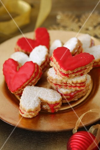 Heart-shaped Christmas biscuits with red icing and icing sugar