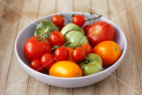 A bowl of red, green and yellow tomatoes
