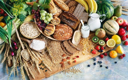 An arrangement of corn, bread, milk, fruit and vegetables