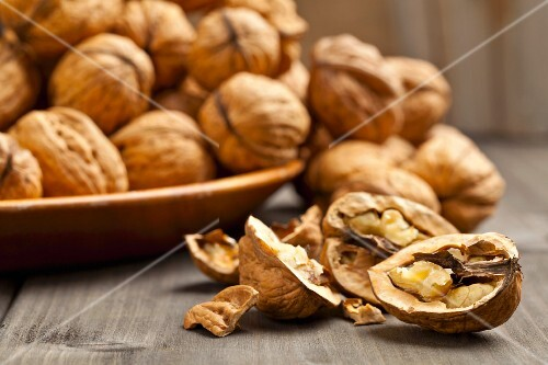 Whole and halved walnuts on a wooden table