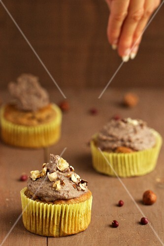 Cupcakes being decorated with sweet bean cream and caramelised nuts