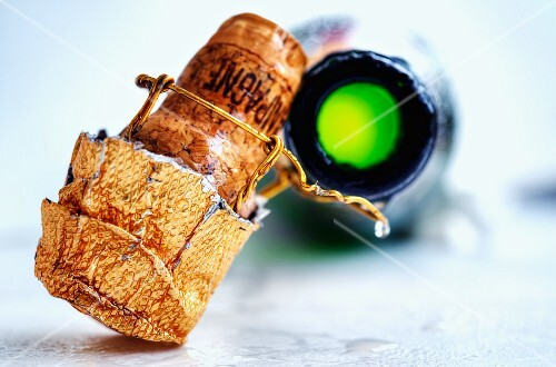A champagne cork and an open bottle of champagne
