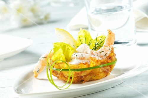 Prawns in a dill and yoghurt sauce with lettuce leaves in a potato nest