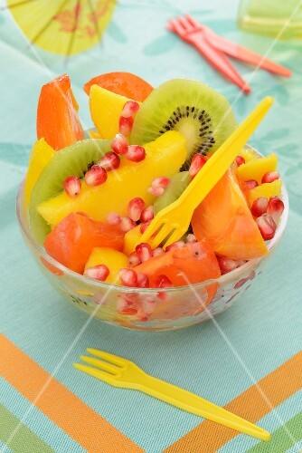 Fruit salad with persimmon, mango, kiwi and pomegranate seeds