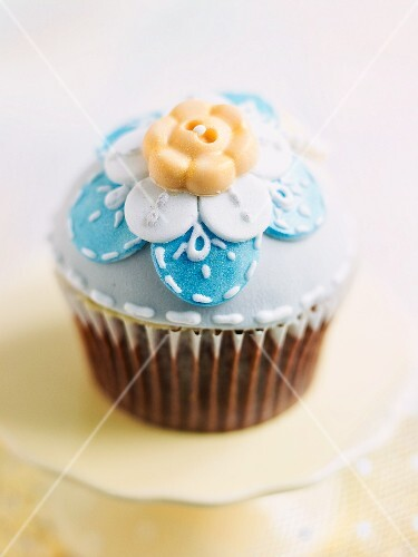 A cupcake decorated with blue icing and a sugar flower