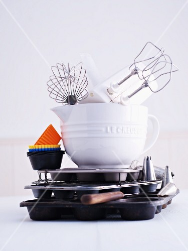 A hand mixer, a whisk, a mixing bowl, muffin cases and a muffin tin