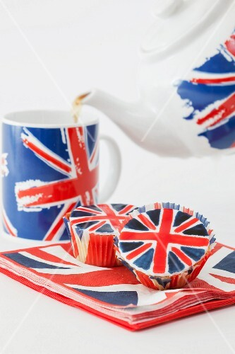 Tea being poured from a Union Jack teapot with matching cupcakes