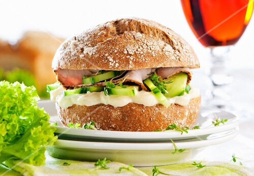 A rye bread roll with cream cheese, cucumber, turkey breast and cress