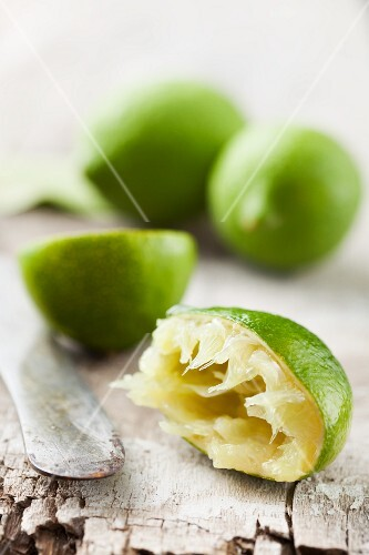 A half juiced lime with whole limes in the background