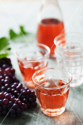 Two glasses of rose wine with a bunch of grapes