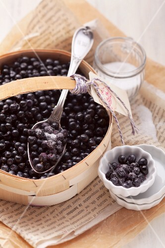 Sugared blueberries in a wooden basket and a tartlet dishes