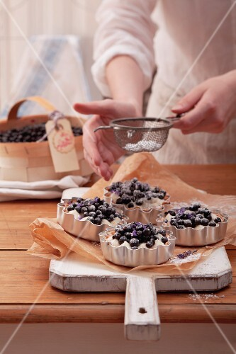 Blueberry tartlets being dusted with icing sugar