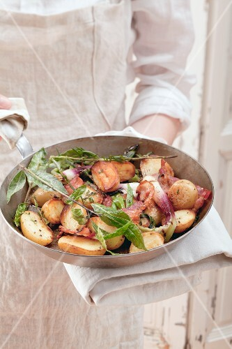 Potatoes and spring onions with herbs in a pan