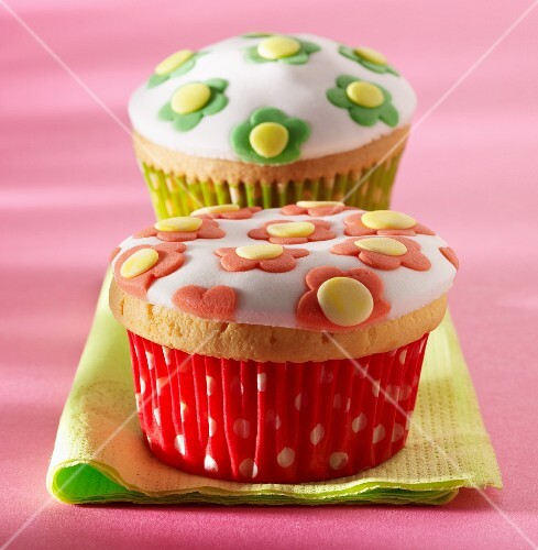 Two cupcakes decorated with flowers