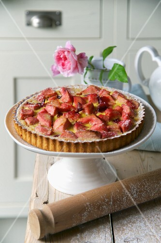Plum and apple tart on a cake stand