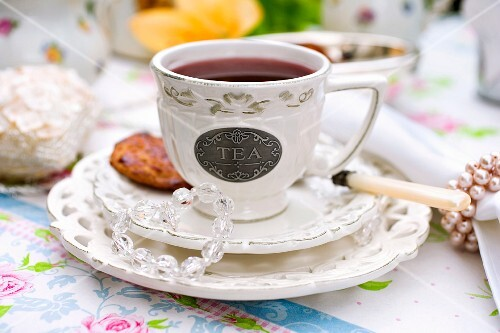 A cup of tea with a tea biscuit on a decorative table