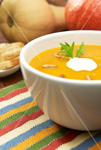 Pumpkin soup with a dollop of cream and roasted pine nuts