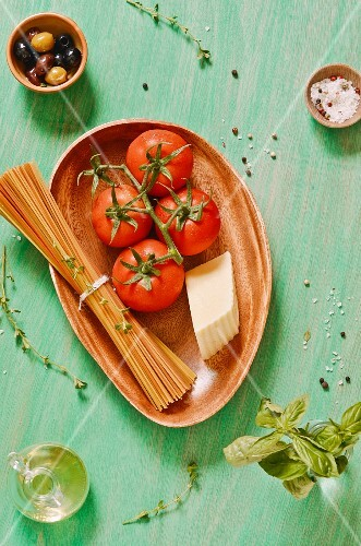 An arrangement of tomatoes, pasta, cheese, basil, spices and olives