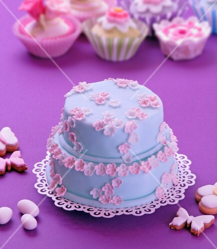 A two tier Easter cake decorated with blue icing and pink sugar flowers