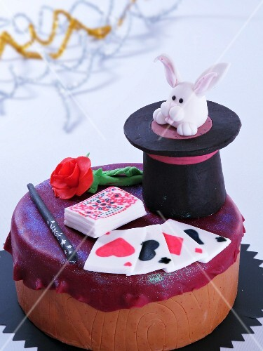 A magic-themed child's birthday cake decorated with playing cards and a magician's hat